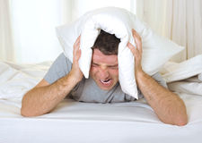 Man suffering hangover and headache with pillow on Royalty Free Stock Image