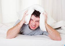 Man suffering hangover and headache with pillow on Stock Images
