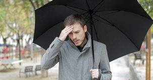 Man suffering head ache under the rain. Angry man suffering head ache walking towards camera holding an umbrella under the rain in a park stock footage