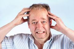 Man Suffering from a Headache or Bad News. A middle-aged man is suffering from a migraine or bad news Royalty Free Stock Image