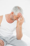 Man suffering from headache in bed Stock Images