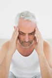 Man suffering from headache in bed Stock Photo