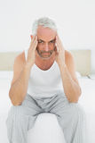 Man suffering from headache in bed Royalty Free Stock Photos