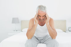 Man suffering from headache in bed Stock Image