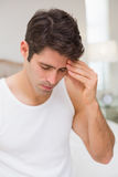 Man suffering from headache in bed. Young man suffering from headache in bed at home Royalty Free Stock Photography