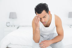 Man suffering from headache in bed Stock Photos