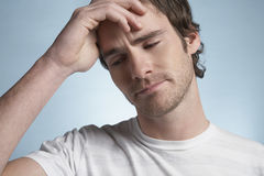 Man Suffering From Headache. Closeup of handsome young man suffering from headache on blue background Royalty Free Stock Photo