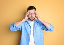 Man suffering from headache. On color background Stock Photography