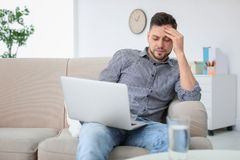 Man suffering from headache. At home Stock Photography