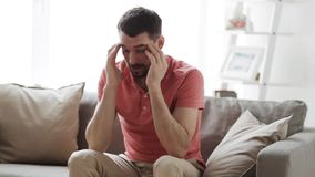 Man suffering from headache at home. Health care, pain, stress, age and people concept - man suffering from headache at home stock footage