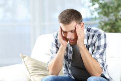 Man suffering headache at home. Man suffering headache sitting on a sofa in the living room at home Stock Photo
