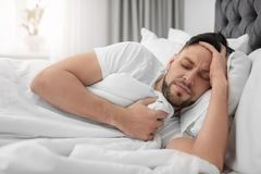 Man suffering from headache while lying on bed. At home Royalty Free Stock Image