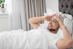 Man suffering from headache while lying on bed. At home Stock Images