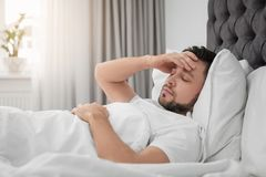 Man suffering from headache while lying on bed. At home Royalty Free Stock Photos