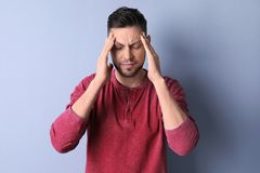 Man suffering from headache. On color background royalty free stock images