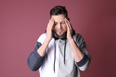 Man suffering from headache. On color background Stock Photos