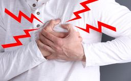 Man suffering from heart attack on color background. Closeup royalty free stock photography