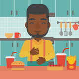 Man suffering from heartburn. An african-american man standing in the kitchen in front of table full of junk food and suffering from heartburn vector flat Stock Photos