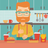 Man suffering from heartburn. A hipster man with the beard standing in the kitchen in front of table full of junk food and suffering from heartburn vector flat Stock Photography