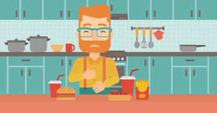 Man suffering from heartburn. A hipster man with the beard standing in the kitchen in front of table full of junk food and suffering from heartburn vector flat Royalty Free Stock Image