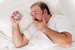 Man suffering from insomnia trying to sleep. Man is suffering from insomnia trying to sleep checking the time on his alarm clock in desperation as he realises he Royalty Free Stock Photography