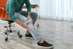 Man suffering from leg pain indoors with space for text. Man suffering from leg pain indoors, closeup with space for text royalty free stock images