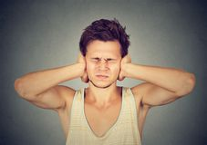 Man suffering from loud noise. Young frustrated man covering ears annoyed with noise from neighbors stock images