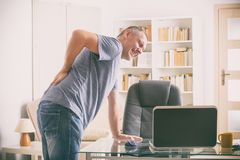Man suffering from low back pain. Man in home office suffering from low back pain standing near desk with notebook, papers and other objects Stock Images