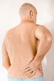 Man suffering of low back pain. Man massaging the low back because of a painful lumbago due to a displacement of the lumbar vertebrae Royalty Free Stock Photos