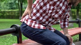 Man suffering lower back pain, reading newspaper in park, compressed nerve roots. Stock photo royalty free stock image