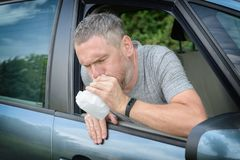 Man suffering from motion sickness. In a car and holding sick bag stock image