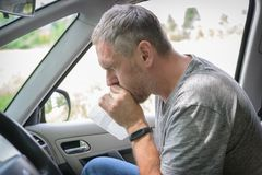 Man suffering from motion sickness. In a car and holding sick bag royalty free stock images