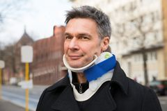 Man suffering from neck ache. Using Cervical Collar stock photos