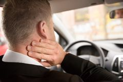 Man suffering from neck pain while driving. Rear View Of A Man Having Neck Pain While Driving A Car Stock Image