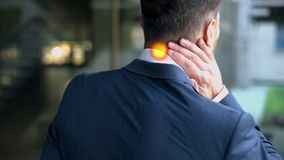 Man suffering from neck pain, muscle spasm, spot indicates inflammation, closeup stock photos