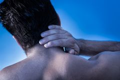 Man suffering from neck pain. Rear View Of Young Man Suffering From Neck Pain Royalty Free Stock Photography