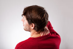 Man suffering from neck pain. Young man suffering from neck pain, horizontal Royalty Free Stock Photo