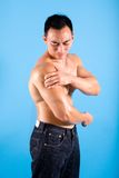 Man suffering from pain and discomfort on shoulde. Muscular man suffering from pain and discomfort on shoulder Stock Photo