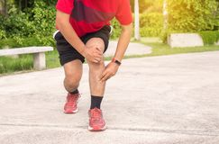 Man suffering from pain in leg injury after sport exercise running jogging and workout. Outdoor stock photo