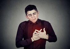 Man suffering from sharp heartache chest pain. Heart disease. Adult man suffering from severe sharp heartache, chest pain. Heart disease concept Stock Image