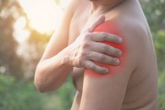 Man suffering from shoulder pain. Acute pain in a man muscle con. Cept with red spot royalty free stock photos