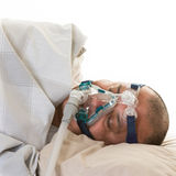 Man suffering from sleep apnea wearing mask Royalty Free Stock Image