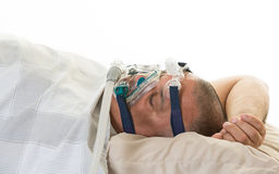 Man suffering from sleep apnea wearing mask Stock Images