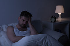 Man suffering from sleeplessness. Sitting in the bed Stock Photography