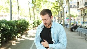 Man suffering stomach ache in the street. Man suffering stomach ache complaining in the street stock footage