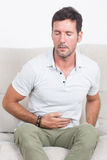 Man suffering from stomachache. Man in white polo shirt sitting on sofa and needs medication Royalty Free Stock Images