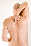 Man suffering of thoracic vertebrae pain. Man massaging his top back, between the shoulders, because of a thoracic vertebrae pain due to a displacement of a Stock Photography