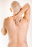 Man suffering of thoracic vertebrae pain. Man massaging his top back, between the shoulders, because of a thoracic vertebrae pain due to a displacement of a Stock Photo