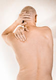 Man suffering of thoracic vertebrae or trapezius muscle pain. Man massaging his top back, the trapezius muscle, because of a thoracic vertebrae pain due to a Stock Images