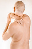 Man suffering of thoracic vertebrae or trapezius muscle pain. Man massaging his top back, the trapezius muscle, because of a thoracic vertebrae pain due to a Stock Photos